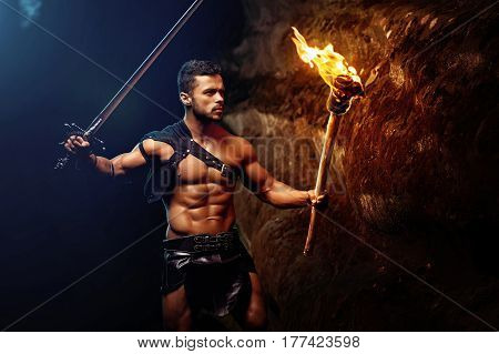 Lighting his way. Horizontal shot of a courageous young warrior holding a sword and a torch lighting his way in the darkness near the rocks