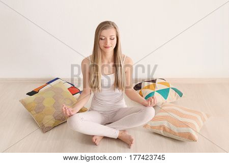 Beautiful young woman meditating prior to sleep while sitting on floor at home