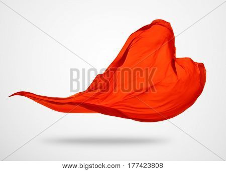 Smooth elegant red cloth separated on gray background. Texture of flying fabric.