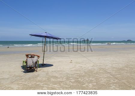 Beach Summer On Vacation Holiday Relax In The Sun On Deck Chairs Under A Umbrella.