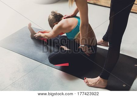 Yoga class instructor helps beginner to make asana exercises. Teacher assists to make sit forward bend pose, Pashimottanasana. Healthy lifestyle in fitness club. Stretching with coach