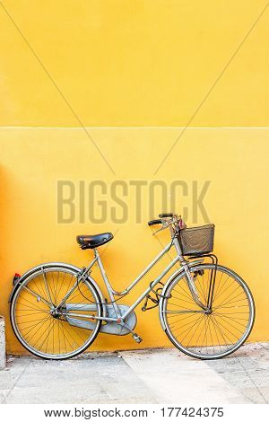 Retro bicycle with basket and yellow wall.
