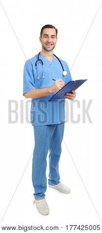 Handsome young medical assistant with clipboard and pen on white background