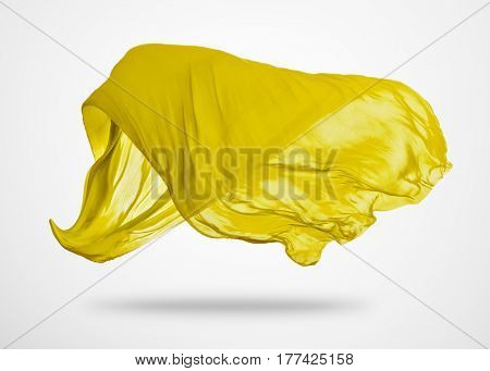 Smooth elegant yellow transparent cloth separated on gray background. Texture of flying fabric.