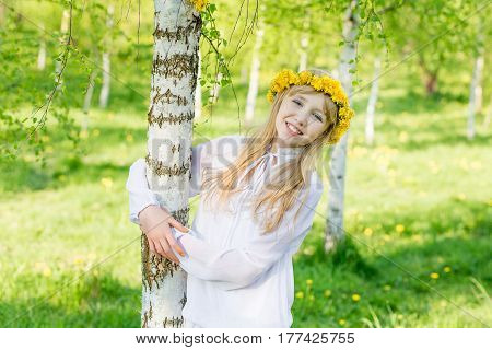 A girl with a wreath of dandelions on her head is standing by the birch