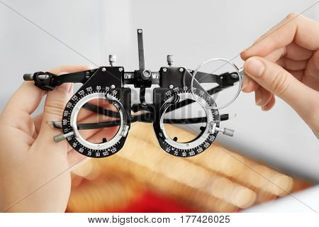 Doctor hands holding frame with trial lenses