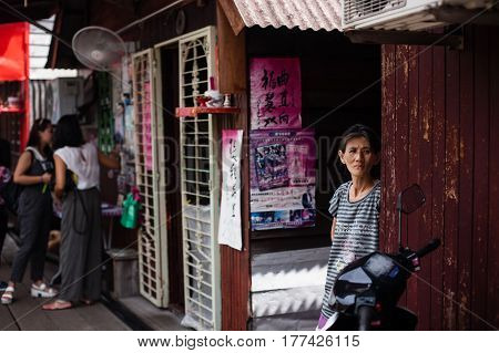 Penang, Malaysia - October 15, 2014: Architecture narrow streets with women. Dirty moldy humidity cityscape