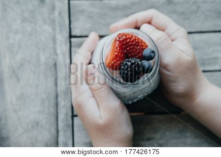 Boy Hands With Pudding With Chia Seeds, Yogurt And Fresh Fruits: Strawberries, Blueberries And Black