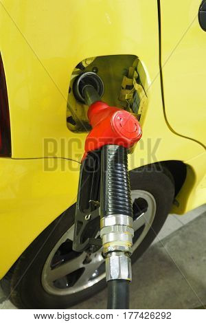 Nozzle fuel Gasohol serving in to the car The door cover has sticker sign silver Gasohol e20 inside Macro photo focus select at handle plastic black color have line texture.