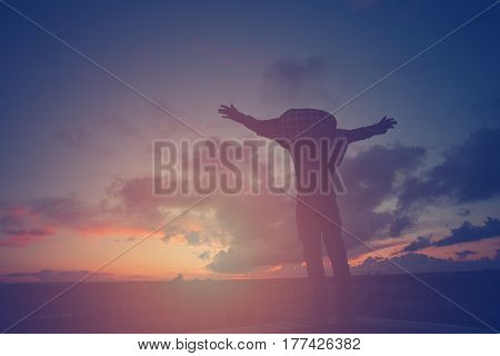 Silhouette of a young active man with outspread hands  on top of the roof at sunset