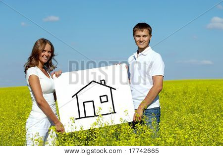 Portrait of happy young couple showing house drawn on paper in meadow