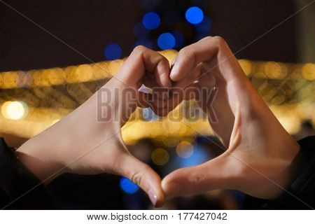 Woman holding hands in heart shape on blurred background