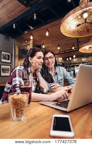 Have a look. Positive delighted brunette putting her hand on the table while looking at laptop, posing sideways