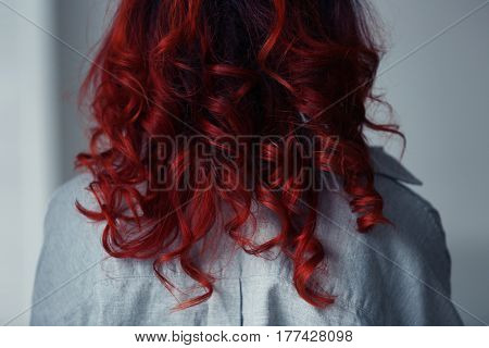 Beautiful young woman with dyed curly hair indoors, closeup