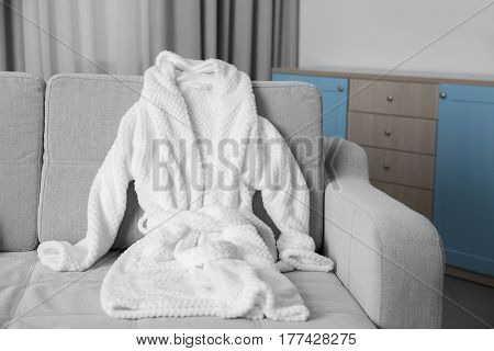 Bathrobe lying on sofa in room