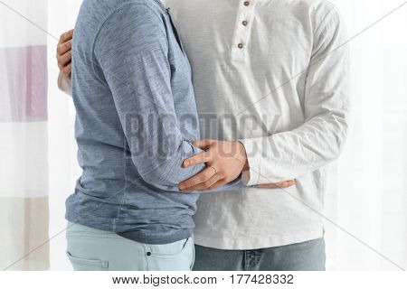 Happy gay couple embracing at home