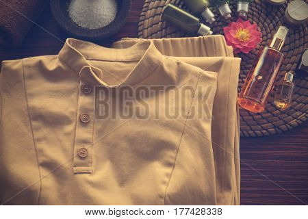 Spa uniform and supplies of masseur on wooden background