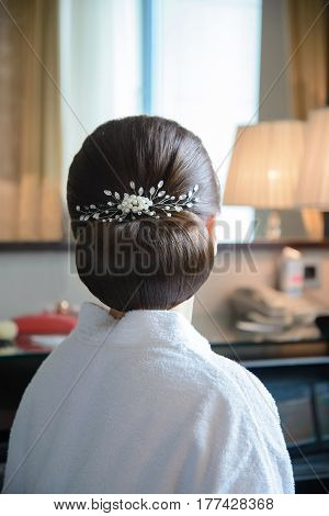 Beautiful wedding hairstyle bride with a white pearl pin in back