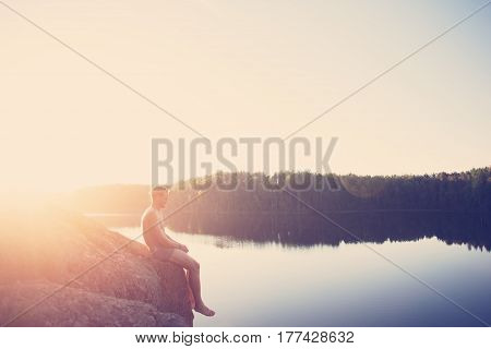 Young man sitting on the edge of the cliff near the lake after swimming and looking far away