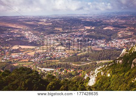 Picturesque medieval towns in valley with storm clouds. Aerial view from Pena Palace in Sintra. Portugal