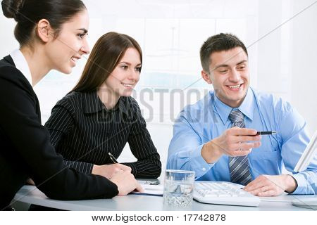 Successful businessman and his pretty colleagues looking at monitor of computer