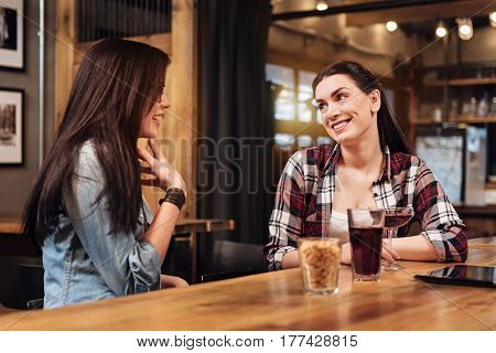 I am very glad. Positive female wearing checked shirt, keeping smile on her face while looking at her friend