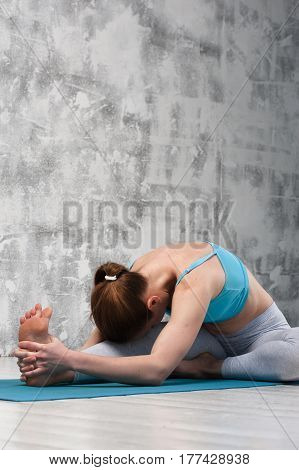 Flexible young woman doing yoga indoors. fit girl wearing sportswear practicing on blue mat against grey wall.