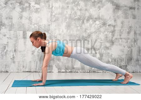 Fit sporty woman doing plank exercise on blue mat. Young woman wearing sportswear doing yoga practice indoors.