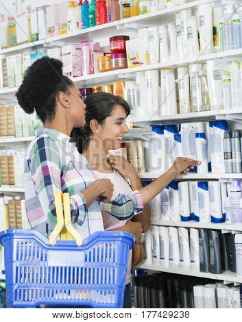 Female Friends Looking At Products In Pharmacy