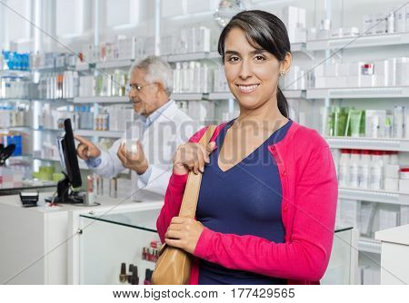 Female Customer Smiling While Chemist Working In Pharmacy