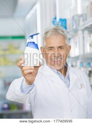 Pharmacist Smiling While Holding Soap Dispenser