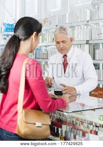 Chemist Swiping Card While Customer Standing In Pharmacy