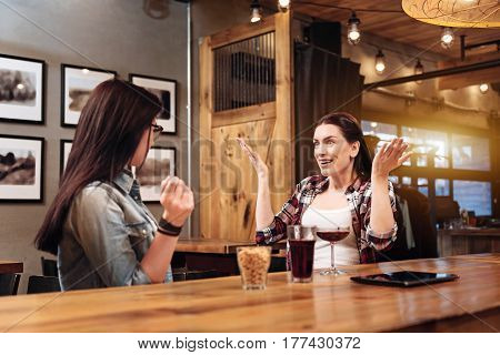 Everything is cool. Satisficed girl sitting opposite her friend, smiling and feeling happy using gesticulation