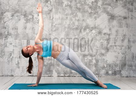 Girl wearing colorful sportswear practicing yoga indoors. Fit sporty woman doing side plank exercise on blue mat.