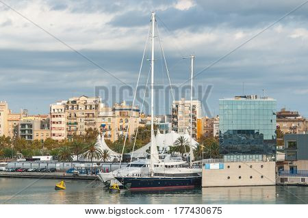 Affluence on display with large yachts & sailboat moored at waterfront spaces. & Condos with a view in afternoon sun in Barcelona.  Cars parked at nearby exhibits under tents.  Tour the world with a yacht.