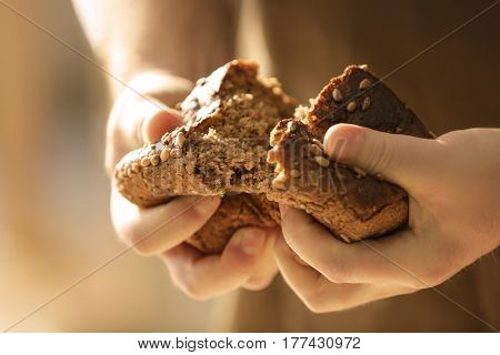 Man breaking off piece of bread, closeup