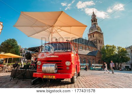 Riga, Latvia - July 1, 2016: Big Red Car Of Street Musicians Buskers Stands Near Cafe On The Dome Square With Dome Cathedral On Background Under Blue Sky In Sunny Summer Day With Blue Sky.