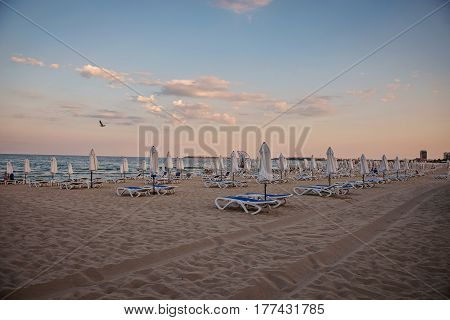 empty chairs stand on beach and close umbrellas. Sunset in Bulgarian seacoast