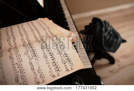 Music notes on black piano, close up