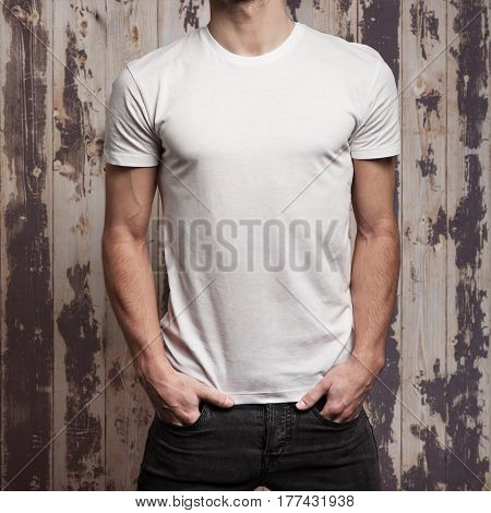 blank white t-shirt on muscle young man and wooden grunge wall background