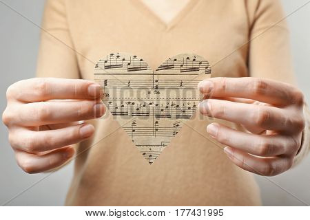 Female hands holding paper heart with notes, music concept