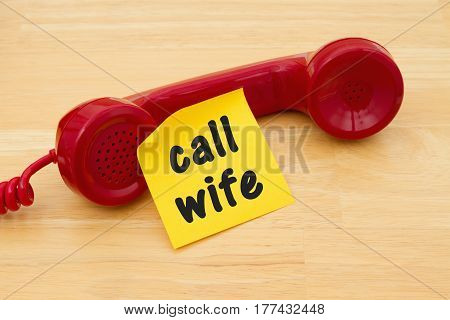 Remember to call your wife Retro red phone handset with a yellow sticky note and text Call Wife