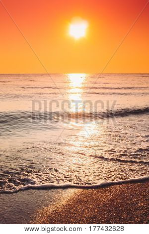 Sun Is Setting On Horizon At Sunset Or Sunrise Over Sea Or Ocean. Tranquil Sea Ocean Waves. Natural Sky Warm Colors.