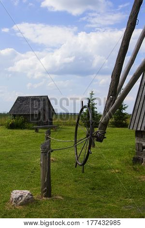 Background landscape view of an old mill, a barn and a field in the museum complex of ancient everyday life Dudutki, Minsk region, Belarus