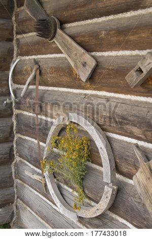 Background landscape view wooden objects of rural life on the wall of a wooden peasant hut in the museum Dudutki, Minsk region, Belarus