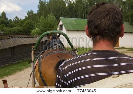 Background view man runs a rural cart with a horse, a museum of rural life Dudutki, Minsk region, Belarus
