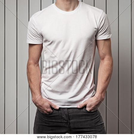 blank white t-shirt on muscle young man and white wooden wall background