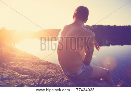 Muscle young man sitting on the cliff near river and looking far away at sunset