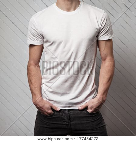 blank white t-shirt on muscle young man and white wall made of wood
