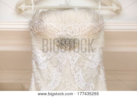 A close up of a white wedding dress hangs on peg, with beautiful silver brooch with many jewels